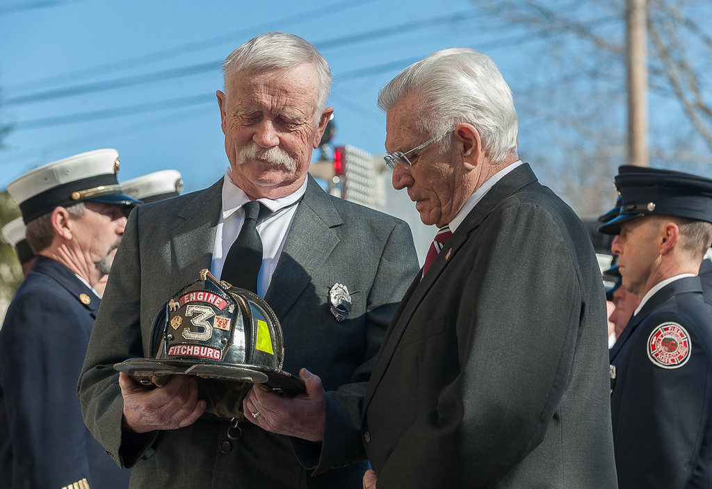. Helmet bearer Ret FF Richard Hawthorne & retired FF Billy Burke look at the helmet of Jack Mulcahy. SENTINEL & ENTERPRISE / Jim Marabello