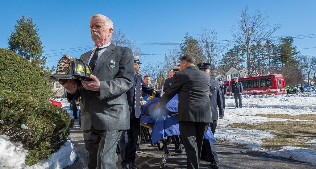 . Helmet bearer Ret FF Richard Hawthorne leads the casket of FF Jack Mulcahy into the church