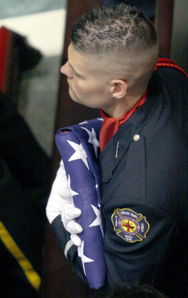 E.L. Hubbard for the Telegraph<br /> A Delhi Township firefighter clutches a flag used to cover one of the caskets during the funeral at the Cathedral of Saint Peter in Chains Wednesday, 04/09/2008. The flag was removed for the funeral service, and draped back onto the casket for the ride to the cemetery.