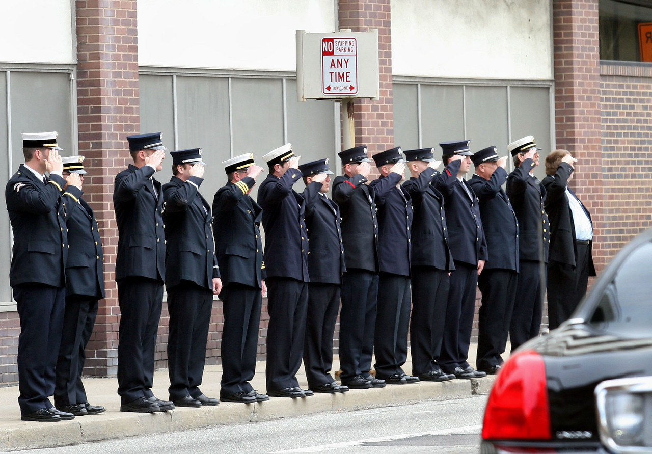 E.L. Hubbard for the Telegraph<br /> Firefighters salute as the families of fallen firefighters Robin Broxterman and Brian Schira leave the Cathedral of Saint Peter in Chains after the funeral service Wednesday, 04/09/2008.