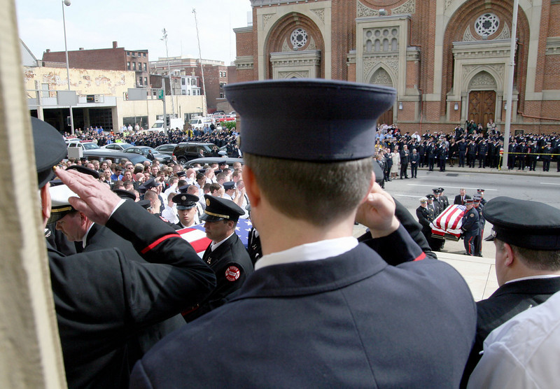 E.L. Hubbard for the Telegraph<br /> Firefighters salute as the caskets are carried into St. Peter in Chains Cathedral for the funeral Wednesday, 04/09/2008.