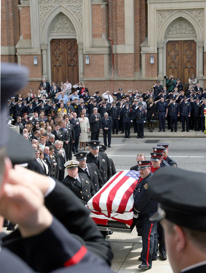 E.L. Hubbard for the Telegraph<br /> Firefighters salute as the caskets are carried past the families and into St. Peter in Chains Cathedral for the funeral Wednesday, 04/09/2008.