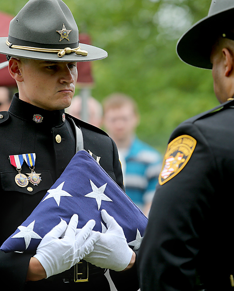 """The flag which covered the casket of former Butler County Sheriff Harold Donald """"Don"""" Gabbard is folded for presentation to his widow during services at Rose Hill Burial Park in Hamilton Saturday, June 4, 2016."""
