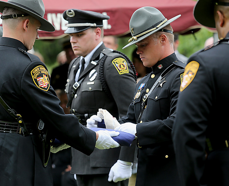 "The flag which covered the casket of former Butler County Sheriff Harold Donald ""Don"" Gabbard is folded for presentation to his widow during services at Rose Hill Burial Park in Hamilton Saturday, June 4, 2016."