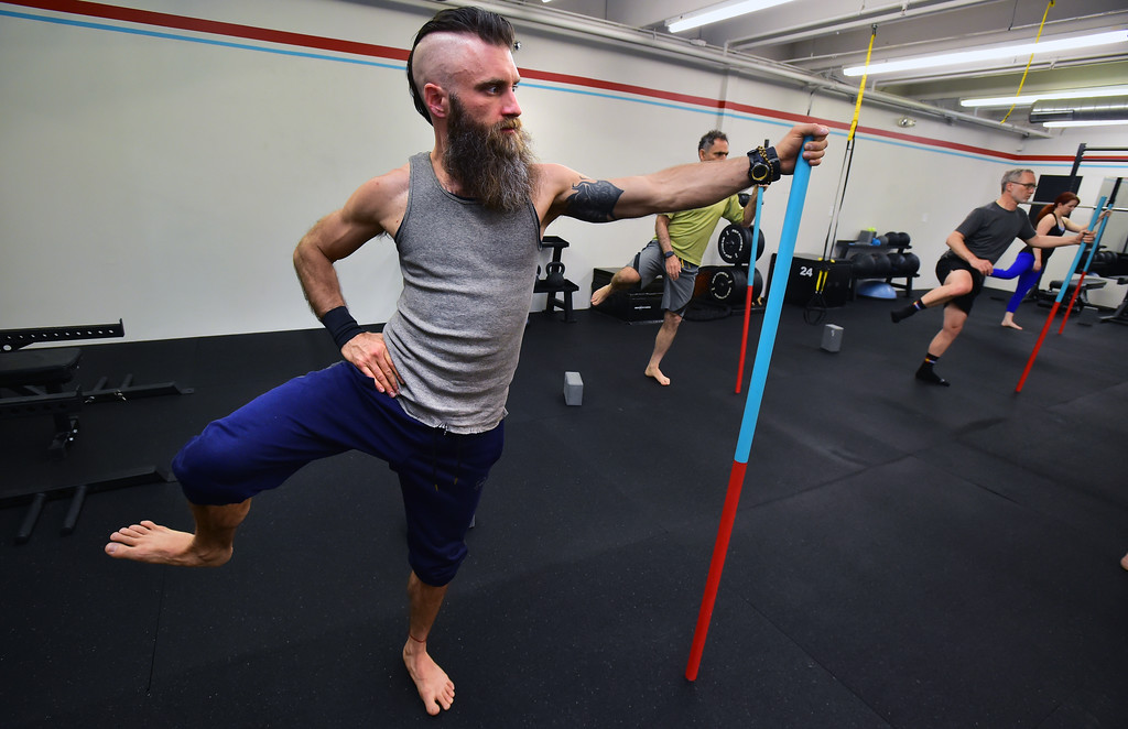 . Casey Maass uses a pole for balance in a stretching posture in the Future Proof Movement Mobility Class on Tuesday in Boulder. For more photos go to dailycamera.com Paul Aiken Staff Photographer April 10, 2018