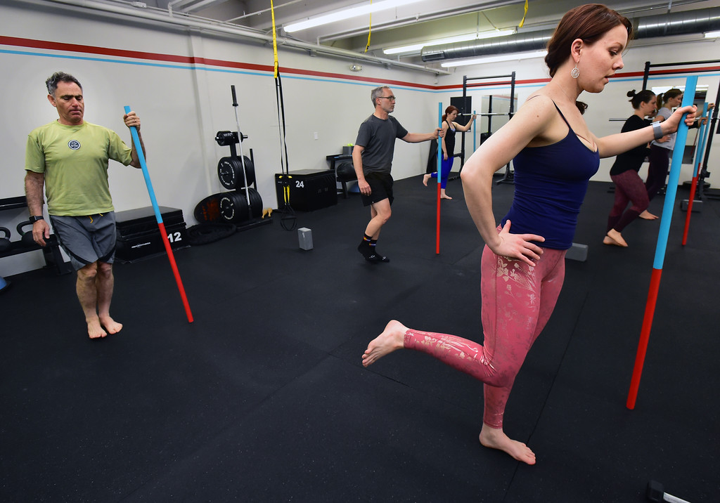 . Rick Epstein and Dulcinea Tincher use poles for balance in a stretching posture in the Future Proof Movement Mobility Class on Tuesday in Boulder. For more photos go to dailycamera.com Paul Aiken Staff Photographer April 10, 2018