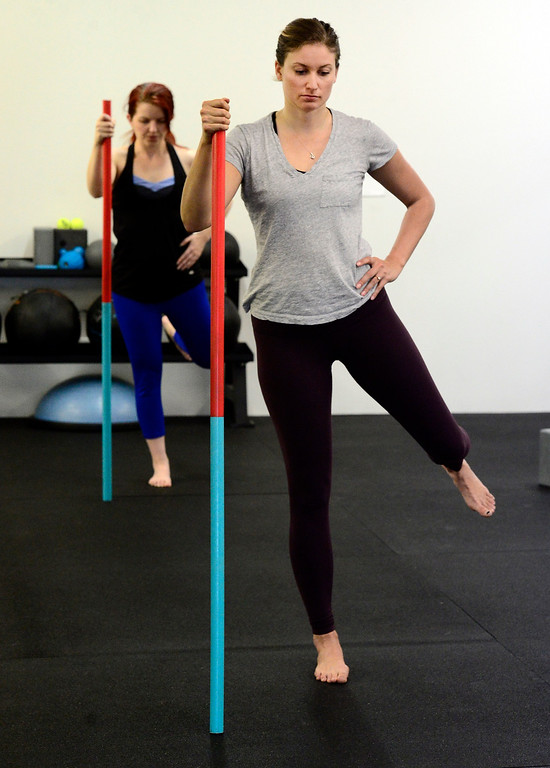 . Casey Scherer uses a pole for balance while working on a hip stretch during the Future Proof Movement Mobility Class on Tuesday in Boulder. For more photos go to dailycamera.com Paul Aiken Staff Photographer April 10, 2018