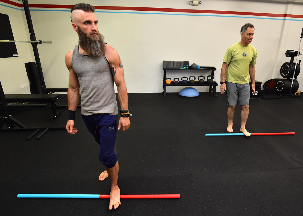 . Casey Maass, left and Rick Epstein roll their feet over poles and work a foot mobility exercise in the Future Proof Movement Mobility Class on Tuesday in Boulder. For more photos go to dailycamera.com Paul Aiken Staff Photographer April 10, 2018