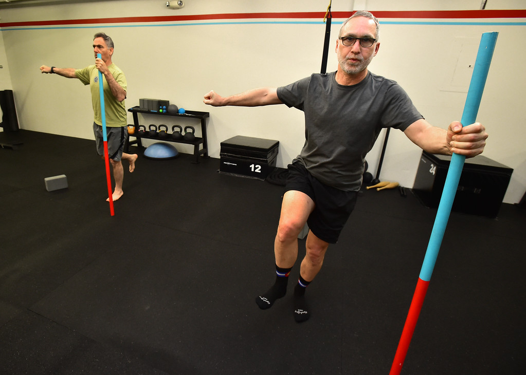 . Rick Epstein, left, and Paul Teven use poles for balance in a stretching posture in the Future Proof Movement Mobility Class on Tuesday in Boulder. For more photos go to dailycamera.com Paul Aiken Staff Photographer April 10, 2018