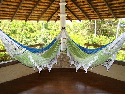 Front veranda with ocean view holds four hammocks from a central column.