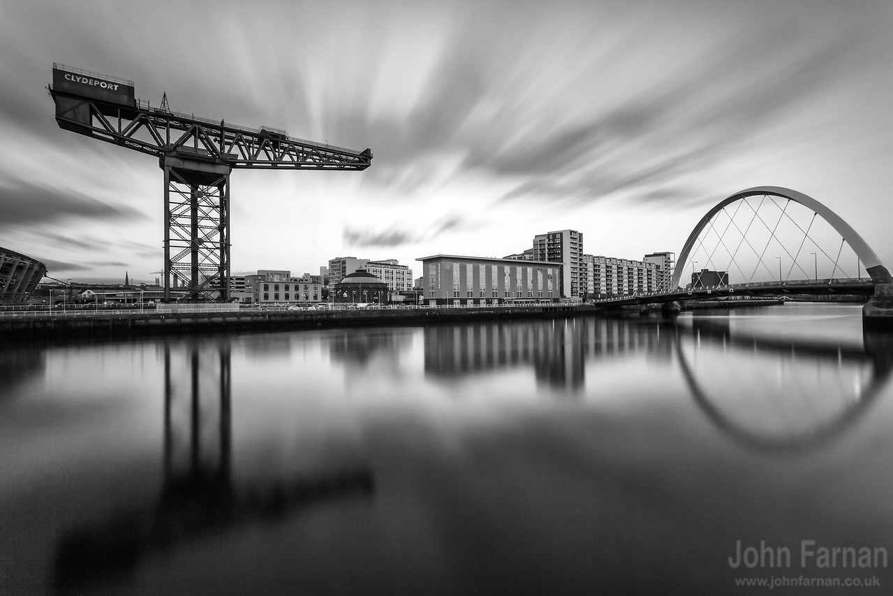 Finnieston crane and the Clyde Arc. Taken in the final moments of daylight on a very cold day. Typical Glasgow. A very long exposure image capturing the movement of the clouds across the sky