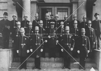 Police officers lined up before teh 75th Precinct in Long Island City sporting the spring and fall uniforms of 1908.  Note the Pot helments worn by some; these were necessary as hoodlums would throw bricks off roofs during riots.