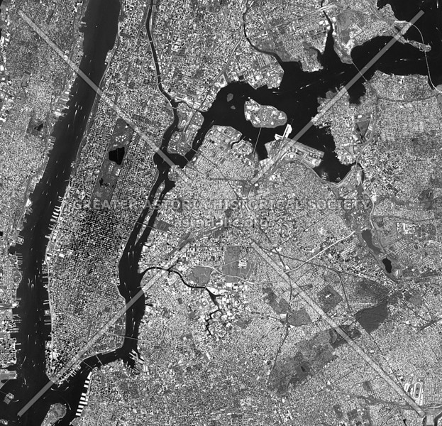 Seen from the edge of space, the East River flows as a narrow ribbon within an urban mosaic.