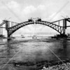 Dramatic view of the Hell Gate Bridge under construction