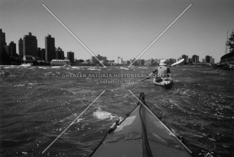 Personal perspective of a kayaker on the East River with a kindred spirit just ahead