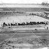 Riker Island inmates taking part in a baseball game whose field is along the East River c. 1930s.  Note Brother Islands in the distance and Port Morris rail yards and power plant in the far distance.
