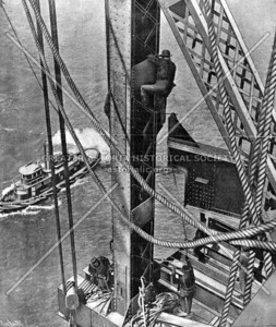 A worker stands on a spire of the bridge 160 feet above the water and more than 500 feet out on a cantilever arm.