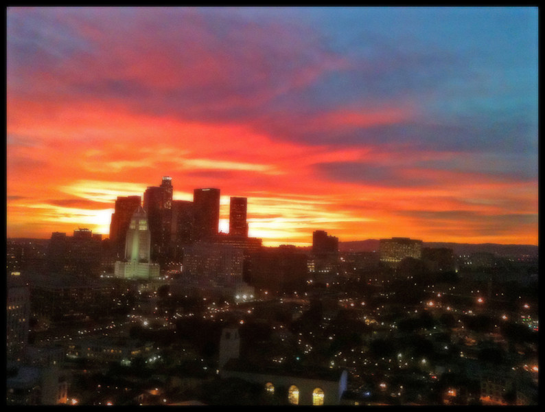 Taken from the MTA building with iPhone 3GS and processed for clarity with Camera+ app. It was spectacular even by L.A.'s high sunset standards. Original had a lot of noise that I cleaned up a little in Photoshop Elements by creating a new layer and using Gaussian Blur on it and then merging with the original. The building with the big windows in the foreground is Union Station, the train depot in L.A.  All in all, not bad for an iPhone but I wish I had my real camera with me. Might have gotten a shot like this: www.laobserved.com/archive/2012/01/tonights_sunset_as_bea...