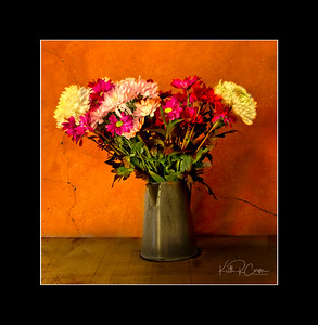 Mixed flowers in a tin pitcher