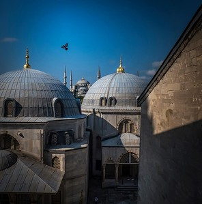 A bird is seen flying over the Blue Mosque in the distance. Photographed through a small window in the Hagia Sophia.