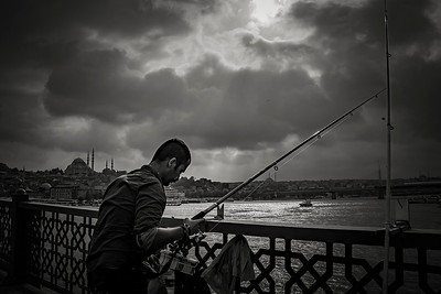 A man fishes from the Galata Bridge which on the Bosporus in Istanbul. The Blue Mosque is seen in the background.