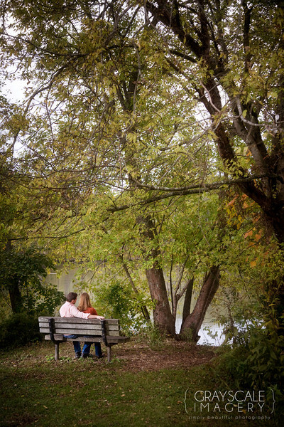 Couple relax on bench by the French Broad River