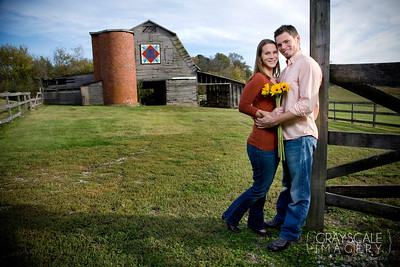 Couple in front of barn with sunflowers