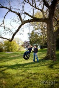 couple on tire swing in tree