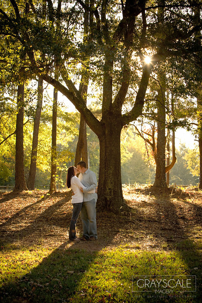kissing as light filters through trees