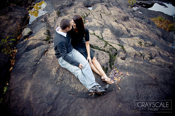 couple kissing on rocks near river