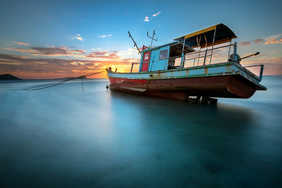 Thai long tail boat at sunrise during low tide Rawai Beach