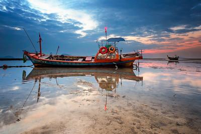 Thai long tail boat at sunrise during low tide Rawai Beach