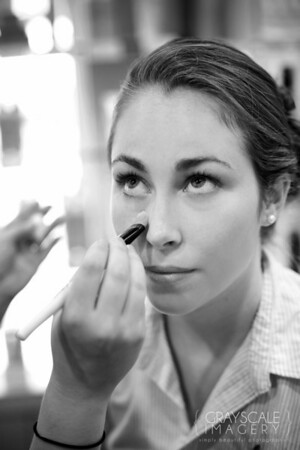 Applying makeup to bridesmaid