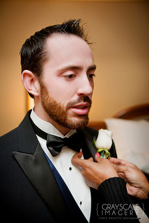 Groomsmen prepare, pinning the boutonniere