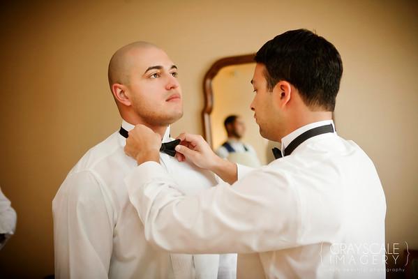 Groom ties Groomsman's bow tie