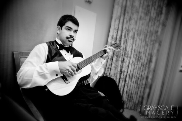 Groomsmen prepare, always time for music, Groomsman with mustache plays guitar