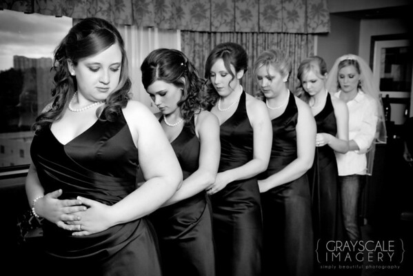 Bridesmaids lace each other's dresses