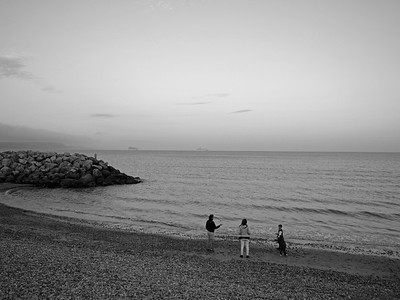 People playing and enjoying at Preston beach, Weymouth, England, UK. Image in black and white