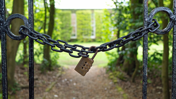 Close up garden gate locked with chain and padlock