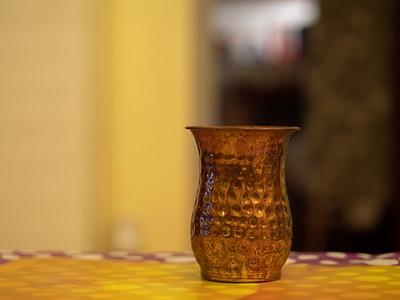 Dented copper mug with blurred background