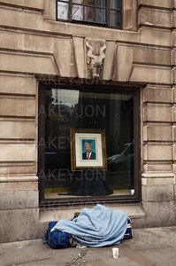 Homeless person under portrait of Nelson Mendela outside South Africa House.