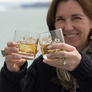 Smiling woman holding glasses of whisky, Lake Argentino, Santa Cruz Province, Patagonia, Argentina