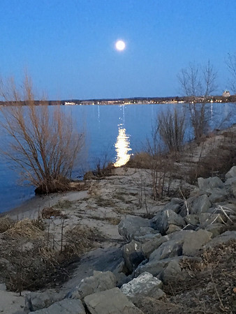 Full moon rising over Traverse City and West Bay in early evening in late April. Photo by Russ VanHouzen.