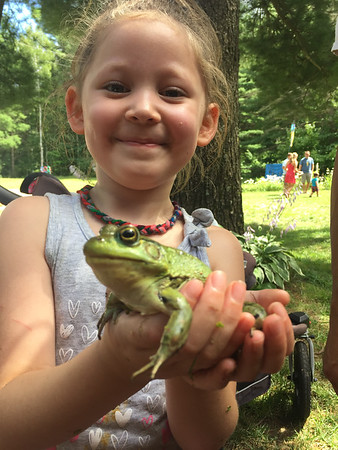 Sadie and a large green frog in Kingsley. Photo by Bill Greene.