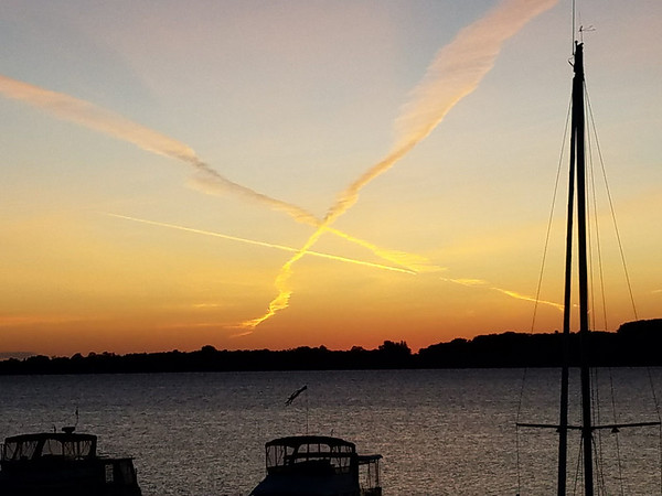 Sunrise over Suttons Bay with aircraft engine exhaust contrails line shaped ice crystals. Photo by RJ Loeher.