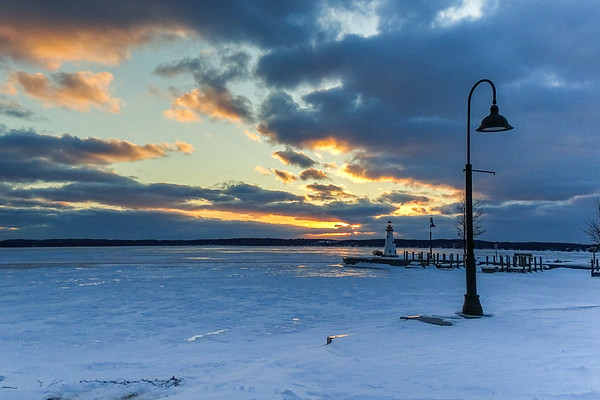 Torch Lake sunset with frozen lake with the lighthouse in the background. Photo by Barbara Lockrey.