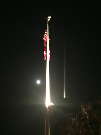 "A flag at the Homestead /Mission Ridge development on Old Mission Peninsula with a small ""super moon"" in the background. Photo by Meredith McComb."