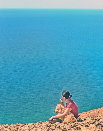 A visitor and her dog enjoy the Lake Michigan view near the Sleeping Bear Dunes overlook. Photo by Gerald Martineau.