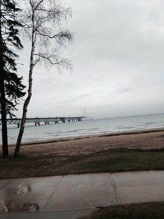 The Mackinac Bridge fades from view during a rain storm as the sun tries to break through. Photo by Sue Gates.