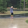 Miles Decker Witt, of San Francisco, enjoying the warm summer rain while visiting his grandparents in Traverse City this summer. Photo by Anne Decker.